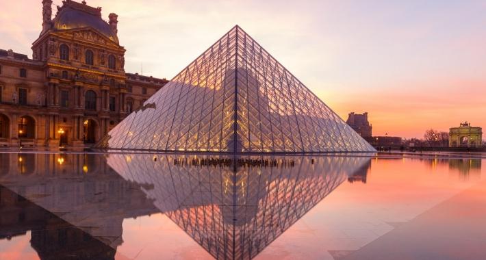 Riflesso sull'acqua della Piramide del Louvre al tramonto. Parigi